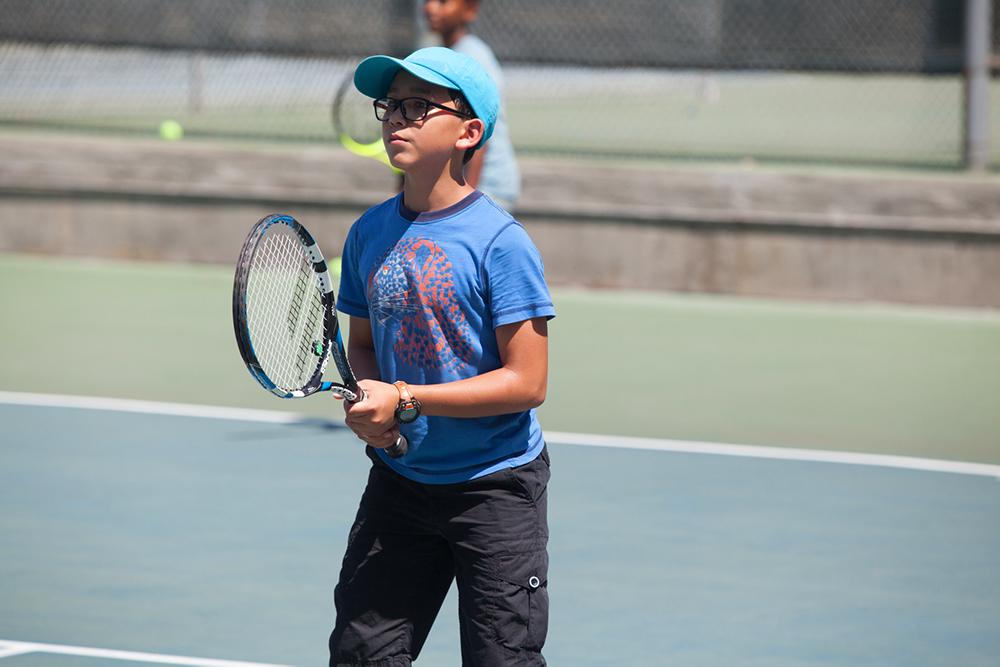 Boy on tennis court with blue cap