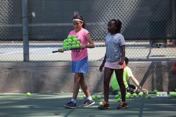 Girls carrying tennis balls