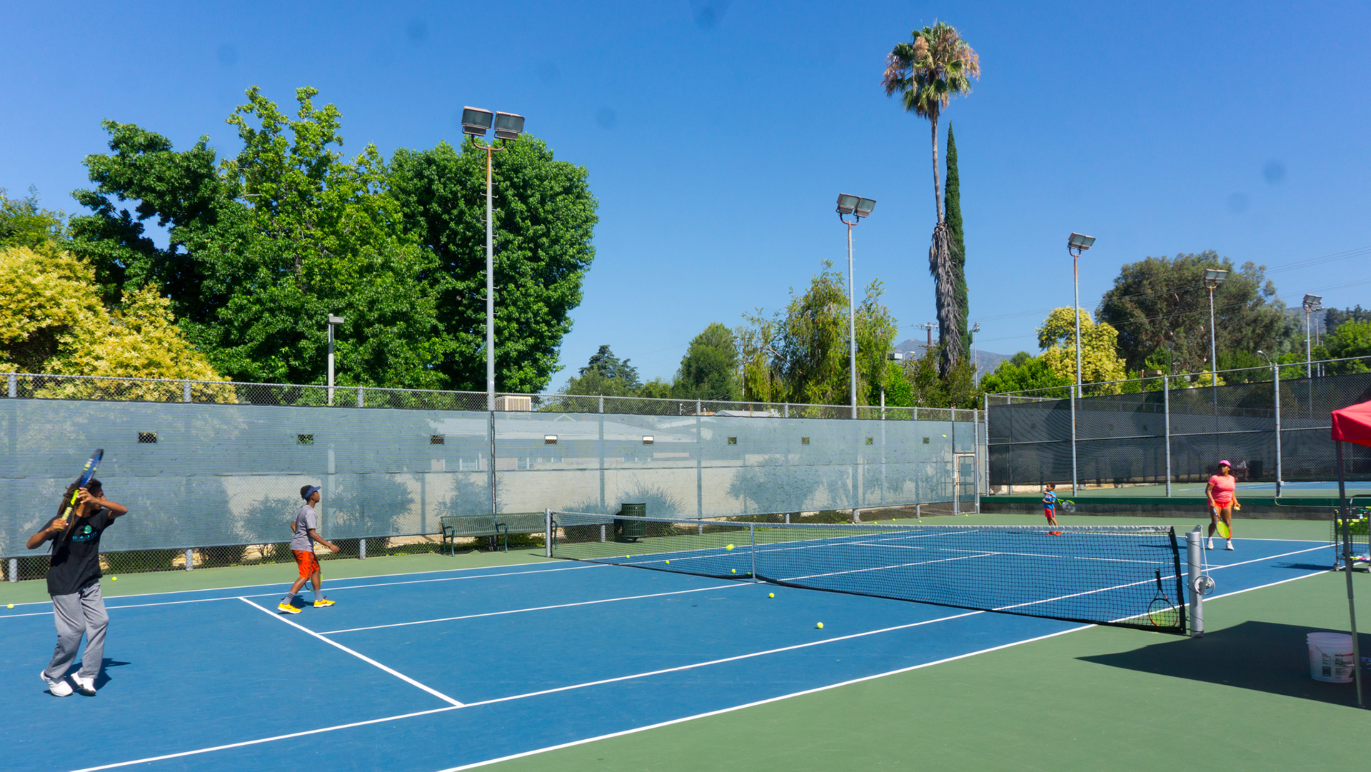 Wide shot Loma Alta Park tennis court with players