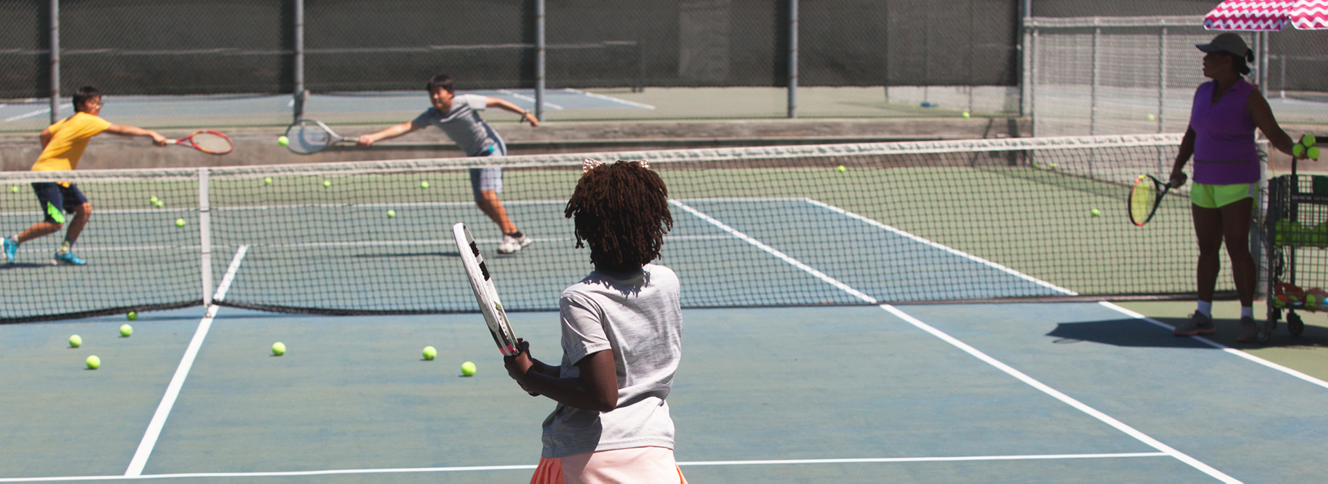 Girl playing against two guys with teacher on court