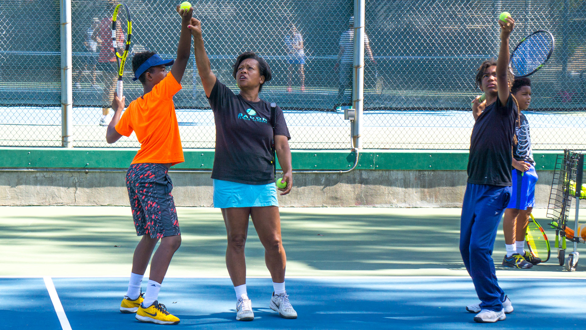 Veronica Badon works with student on his serve