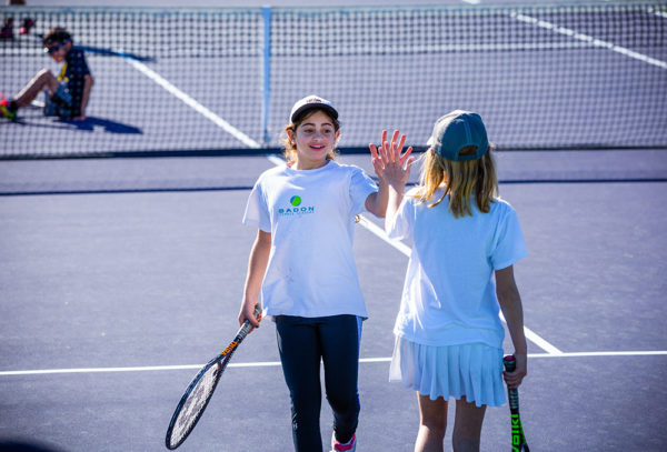 Girls 10 and under high fiving during tennis match Indian Wells