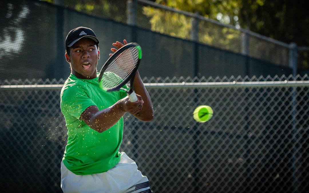 J.B. Badon plays tennis in a green t shirt