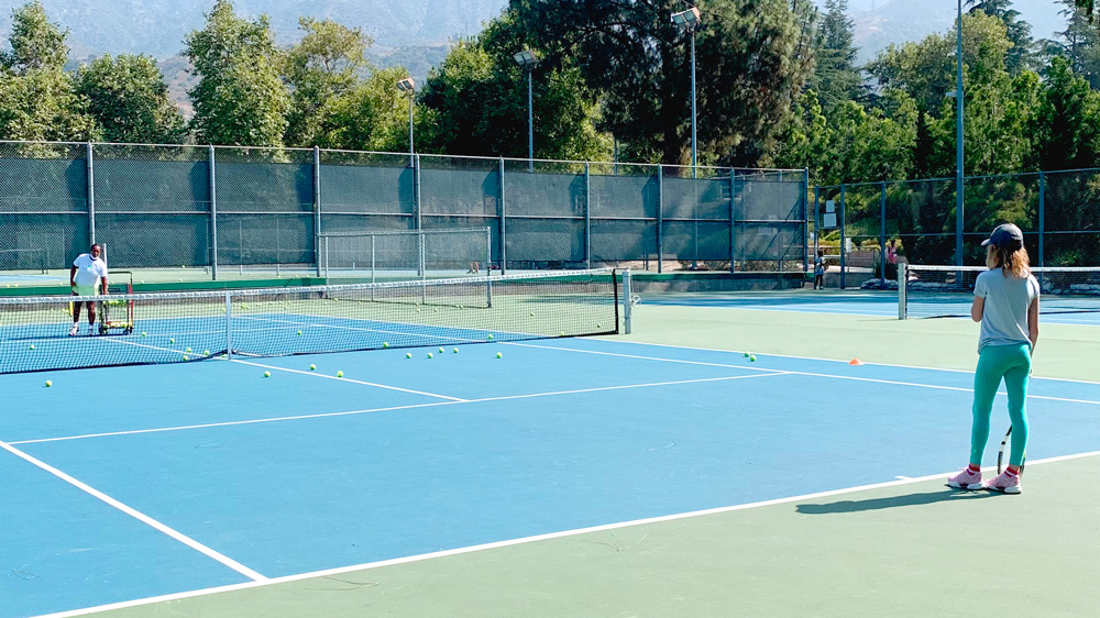private lesson in progress on tennis court