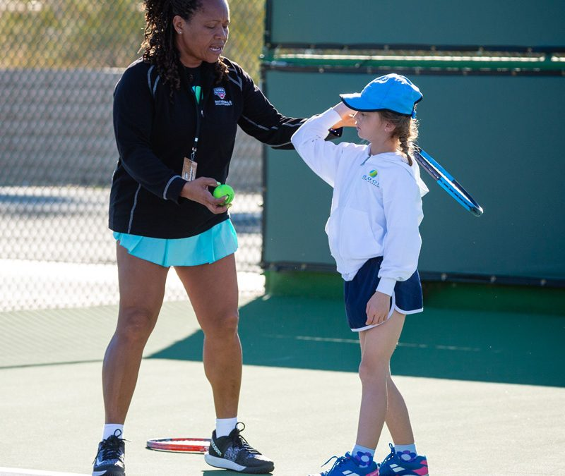 Veronica Badon coaching a student on tennis court at Indian Wells